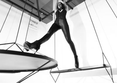 Interior photography of a model striding from suspended furniture