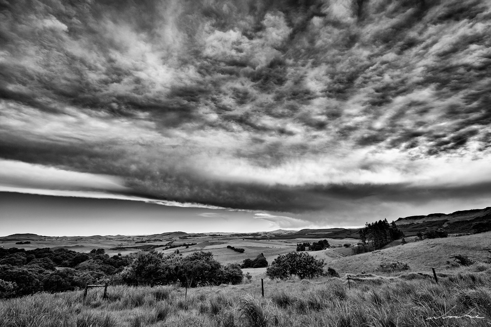 Black and white of Boston Valley in KZN Midlands beneath a dramatic sky