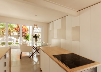 Interior photography showing minimalist kitchen and dining room