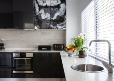 Interior photography showing a modern kitchen with custom painted cupboard doors