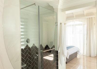 Interior photography of a bathroom and bedroom reflected in the bathroom mirror
