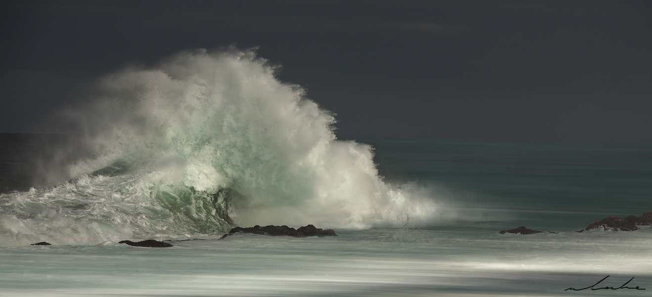 A colour photograph of a wave breaking against some rocks making a fan-like formation
