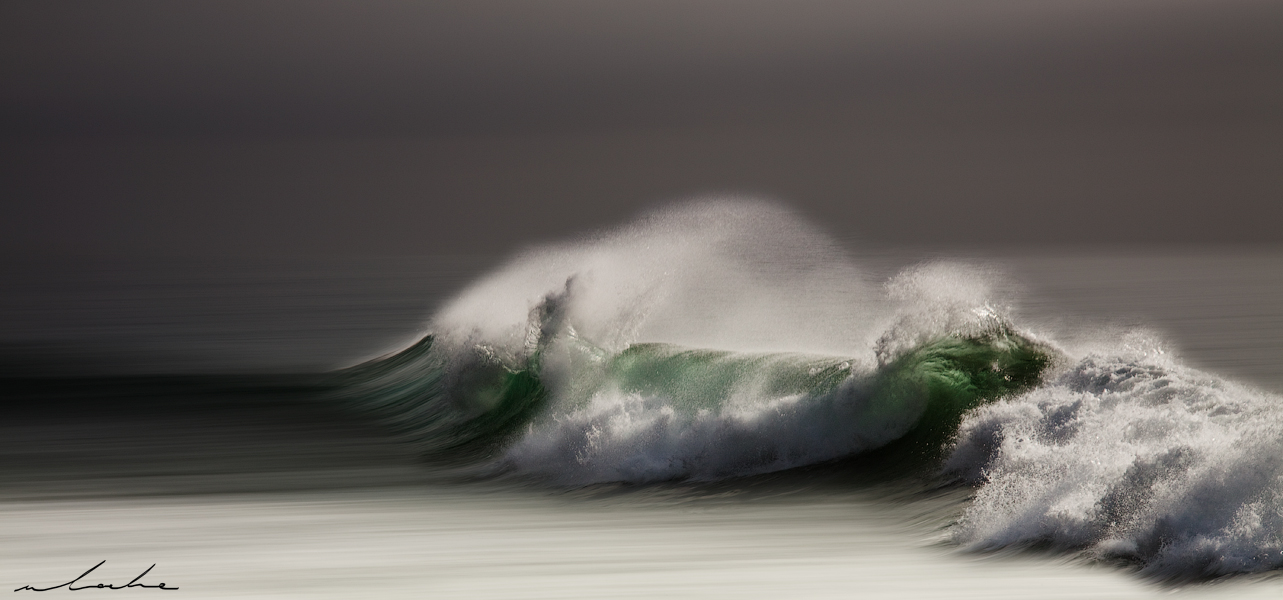 A moody colour photograph of a wave breaking
