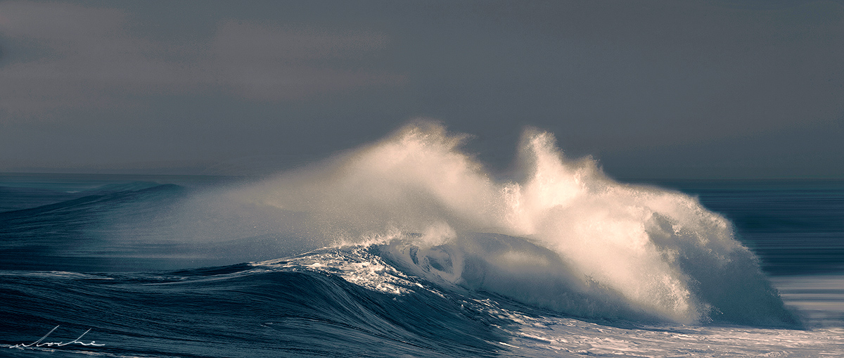 A toned photograph of a single wave rolling in towards the beach